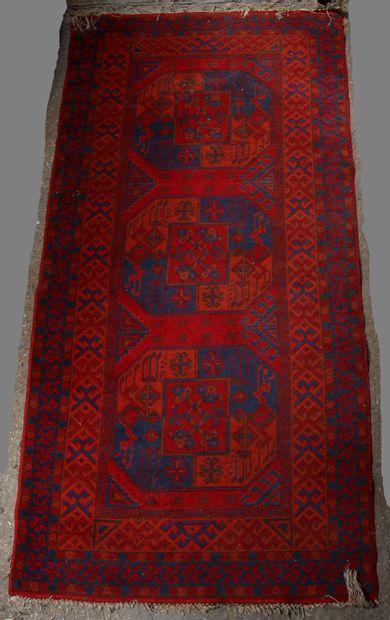 Tapis en laine à fond rouge à décor de trois...