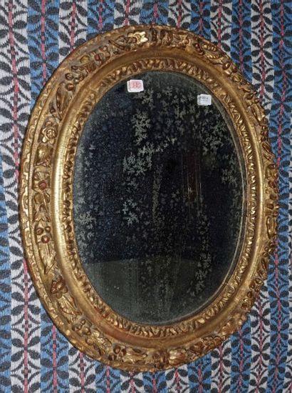 Miroir ovale en bois sculpté et doré à décor...