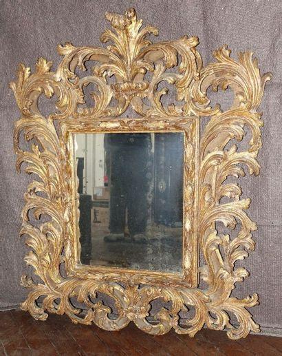 Miroir en bois richement sculpté, doré et...