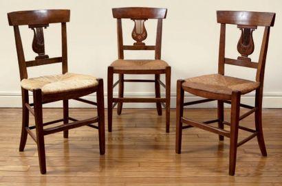 Suite de six chaises paillées en merisier, le dossier à décor ajouré d'une lyre....