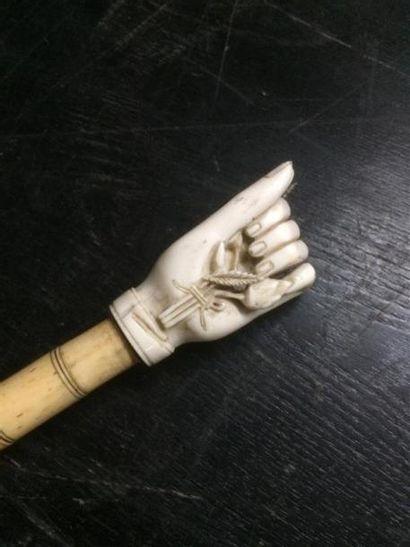 Une pipe à opium en os et matière composite à décor d'une main serrée tenant des...