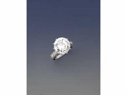 Bague sertie d'un diamant solitaire de forme ronde et de taille brillant, la monture en platine à dix griffes ornée de six petits diamants ronds. Poids brut : 7 g Tour de doigt : 53 Accompagnée d'un rapport de classification du L.F.G. n° 195791 daté du 07/10/2011, précisant :  Poids : 6.85 ct Couleur : J Pureté : SI2.