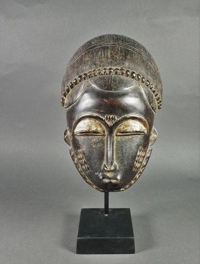 Masque de style baoulé en bois patiné représentant...