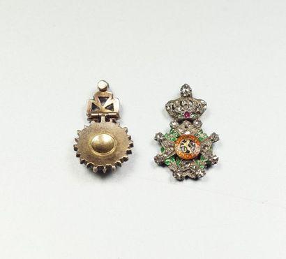 Deux petites breloques figurant des décorations militaires en argent (800/oo) et...