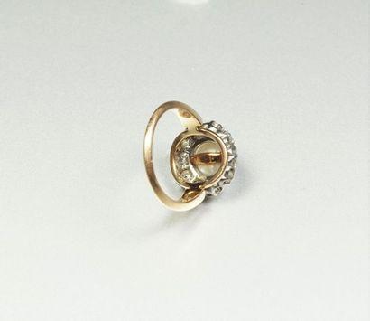 Bague ancienne en or jaune 18K (750/oo) et platine (850/oo) centrée d'une perle...