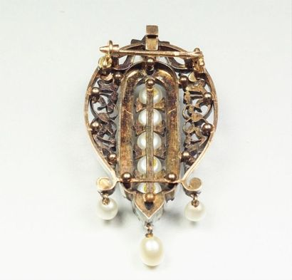 Broche en argent (800/oo) et or jaune 18K (750/oo) centrée d'une ligne de perles...