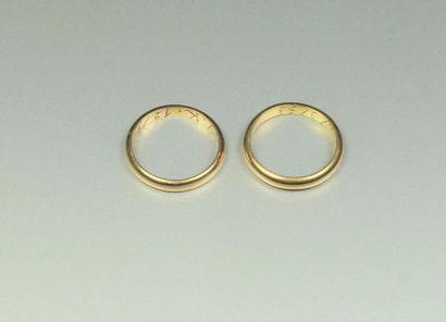 Lot en or jaune 18K (750/oo) comprenant deux alliances lisses, gravées à l'intérieur....