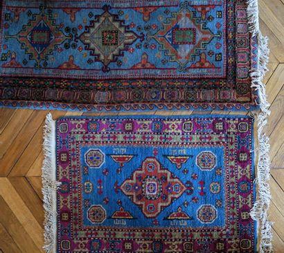 Deux tapis à décor géométrique fond bleu...