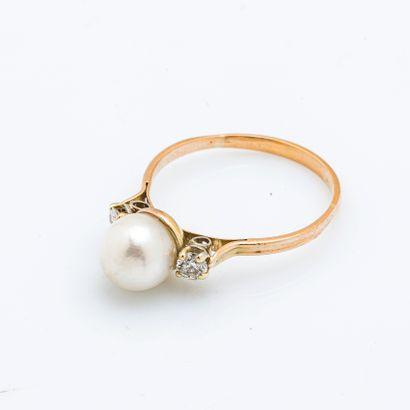 Bague en or jaune 18 carats (750 millièmes) sertie d'une perle épaulée de deux diamants...