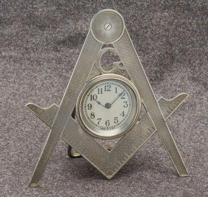 Pendulette en métal argenté formant le compas...