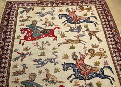 TAPIS à décor de cavaliers et animaux sauvages...