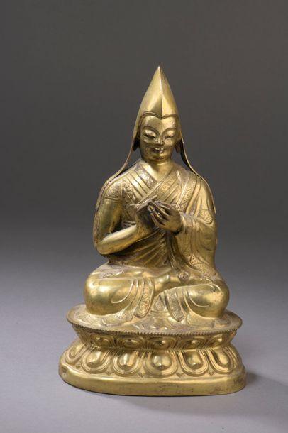 TIBET - XVIe siècle Statuette en cuivre repoussé et doré de lama assis en padmasana...