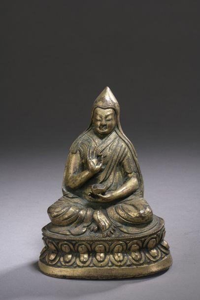 TIBET - XVIIe siècle Statuette de Lama en laiton doré assis sur un socle en forme...