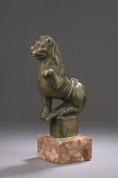 LION en bronze représenté assis, la patte...