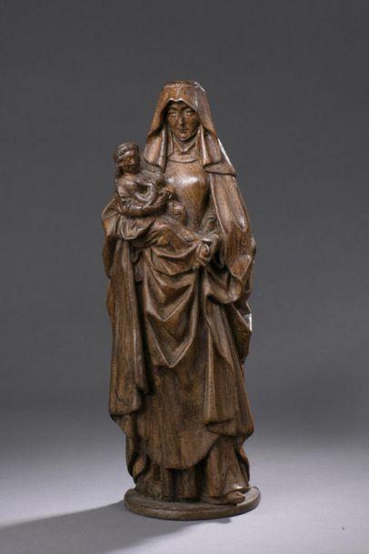 Sainte-Anne Trinitaire en noyer sculpté, dos ébauché. Debout, la sainte porte dans...