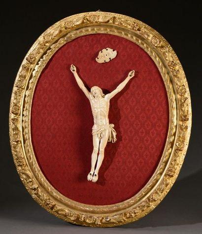 ** Important crucifix en ivoire, Christ expirant. Dans un cadre ovale en bois doré...