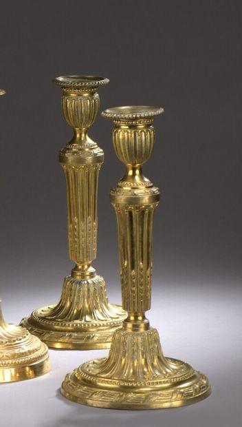 Paire de flambeaux en bronze doré à fût à cannelures rudentées à asperges. Base...