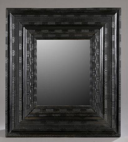 Miroir dans un grand cadre en bois noirci...