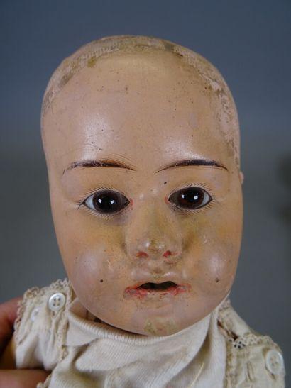 Lot de trois poupées :  - une poupée tête en carton bouilli, corps en skaï, traits...