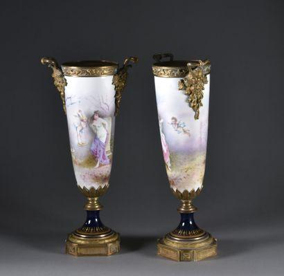 Dans le goût de SEVRES  Paire de hautes cassolettes en porcelaine, à décor antiquisant...