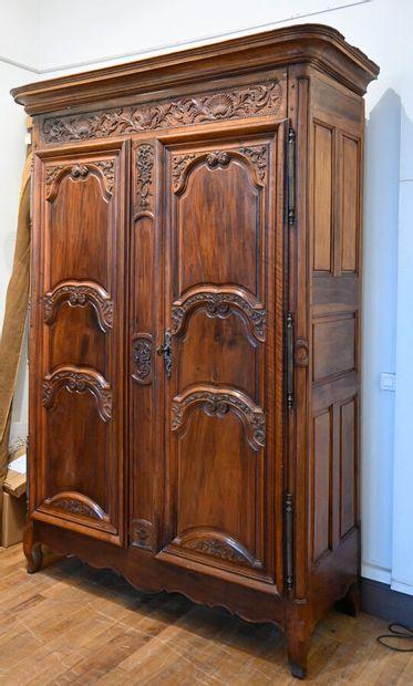 Grande armoire en noyer mouluré ; elle ouvre à deux portes à trois panneaux mouvementés...