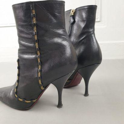 VUITTON  Paire de bottines en cuir noir à effet de découpes gansées d'une chaîne...