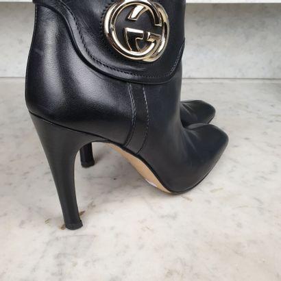 GUCCI  Paire de bottines en cuir noir à effet de revers siglé en métal argenté,...