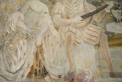 Tapisserie à décor d'un couple galant assis dans un paysage, lui jouant du luth,...