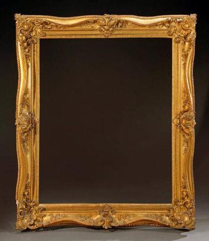 Grand cadre à doucine en bois et stuc doré,...