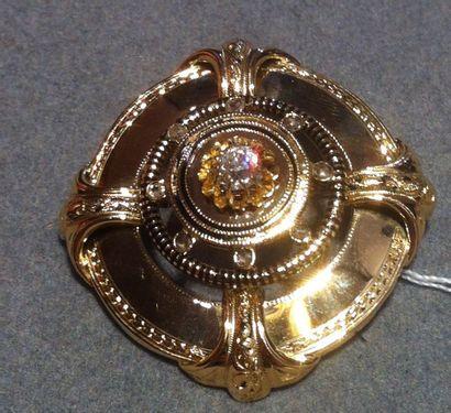 Broche ancienne, de forme ronde, en or jaune ornée en son centre d'un diamant taille...