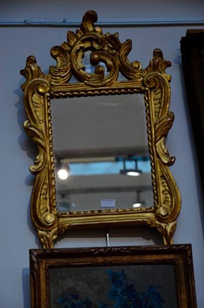 Miroir en bois doré et sculpté d'enroulements et feuillages. Fronton à parecloses....