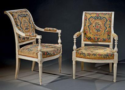 Paire de fauteuils en bois mouluré relaqué blanc à dossier renversé, les pieds fuselés...