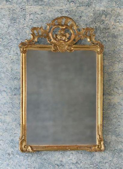 Miroir en bois doré et sculpté, fronton ajouré d'une large coquille. XVIIIe siècle....