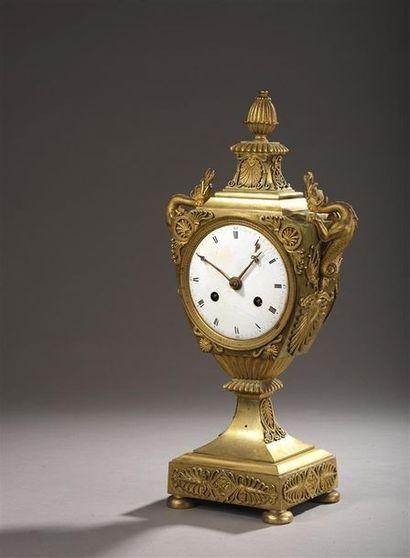 Pendule en bronze doré en forme d'écusson...