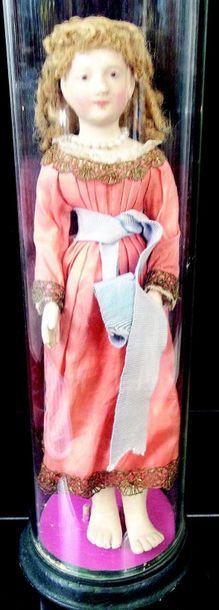 Petite poupée présentée sous globe de verre...