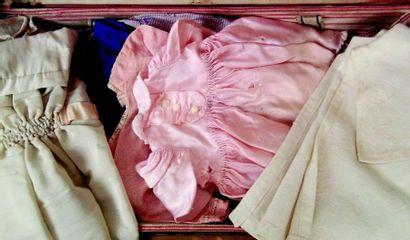 Malle de poupée avec trois séparateurs et nombreux vêtements de petites tailles...