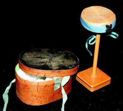 -Un carton à chapeau en copeaux de bois et contenant un chapeau de paille de genre...