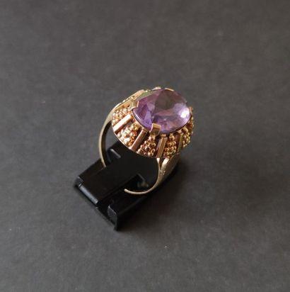 Bague en or 18K (750), sertie d'une améthyste de forme ovale, la corbeille ornée...