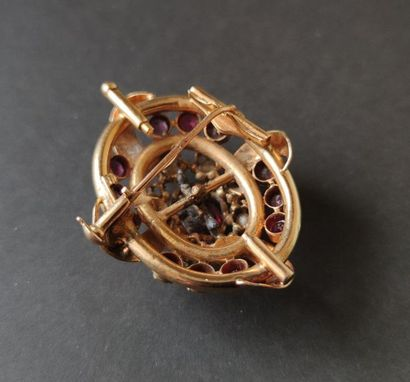 Oval brooch in 18K (750) gold, centered on a garnet in a half pearl surround, the...