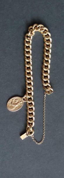 BRACELET gourmette en or jaune 750°/°° à maillons avec médaille Saint Christophe...