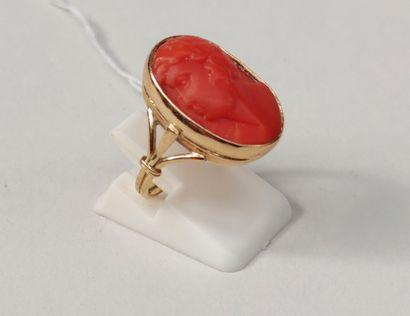 BAGUE, monture en or jaune ornée d'un cabochon de corail rouge à motif d'un profil...