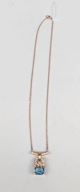 A pendant necklace in yellow gold 750°/00 set with a blue stone and brilliant cut...