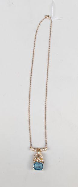 Un collier pendentif en or jaune 750°/00 serti d'une pierre bleu et de diamants...