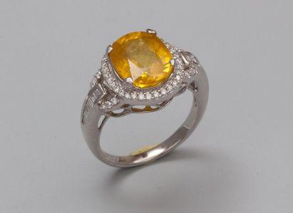 Bague en or gris 750°/00 (tête d'aigle) sertie d'un saphir jaune ovale de 5.09 carats...
