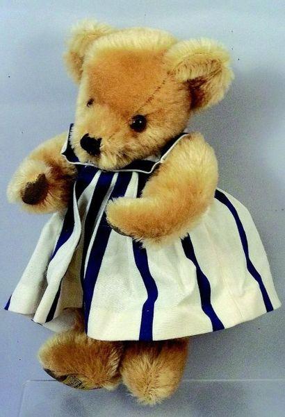 Teddy blond en peluche de marque anglaise MERRY THOUGHT. H 25 cm. Robe rayée d'...