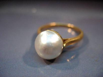 Bague en or sertie d'une demi perle de culture...
