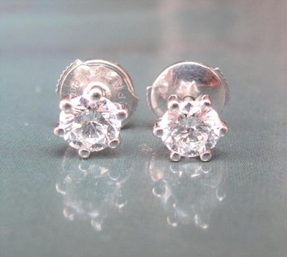 Paire de puces en or gris 750°/00 serties chacune d'un diamant taille brillant de...