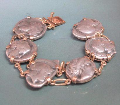 Bracelet en or jaune 750°/00 (tête d'aigle) serti de  six pièces antiques en argent. 60.10 g. L : 16