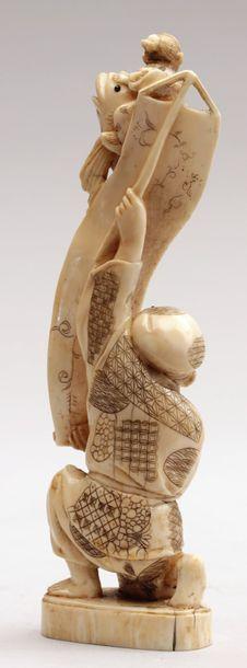 OKIMONO en ivoire représentant un homme déroulant un kakemono duquel émerge et se...