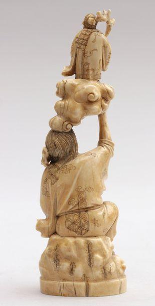 OKIMONO en ivoire représentant Kinko assis sur un rocher tenant un bâton noueux...